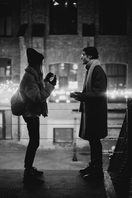Grayscale Photography of Talking Man and Woman