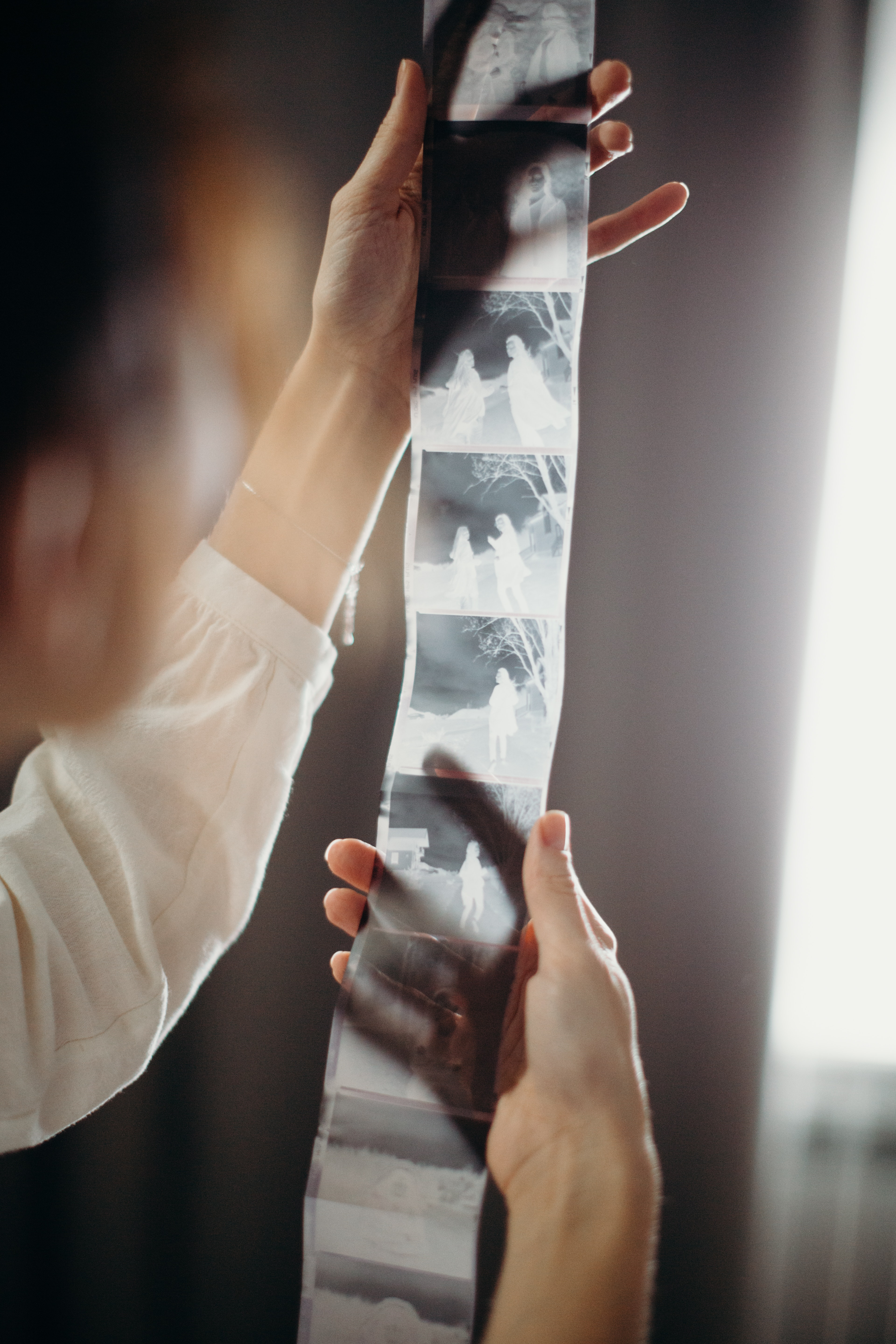 Person holding film strip in front of a laptop.   Photo: Pexels