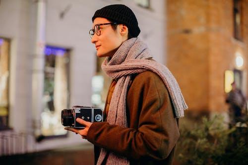 Foto profissional grátis de abrigo, borrão, cachecol, câmera analógica