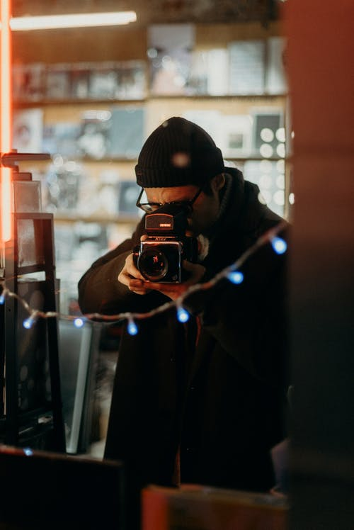 Selective Focus Photography of Man Using Black Camera