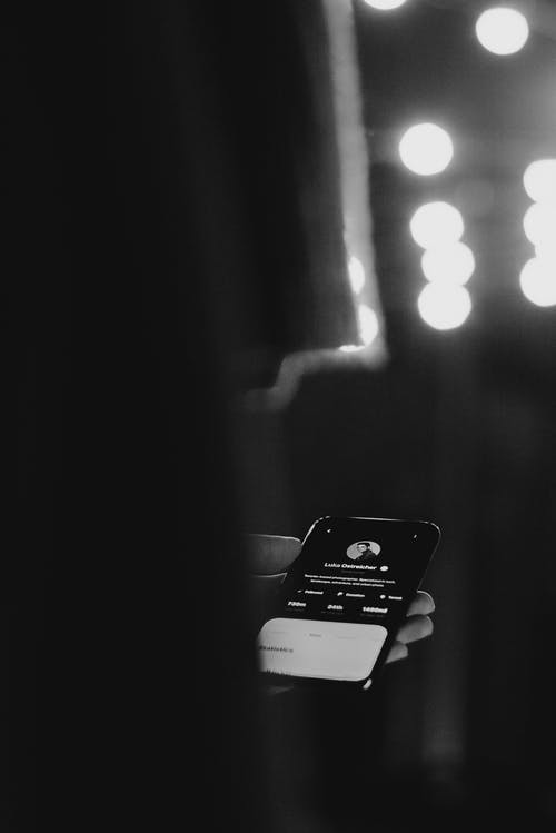 Monochrome Photo of Person Holding Smartphone