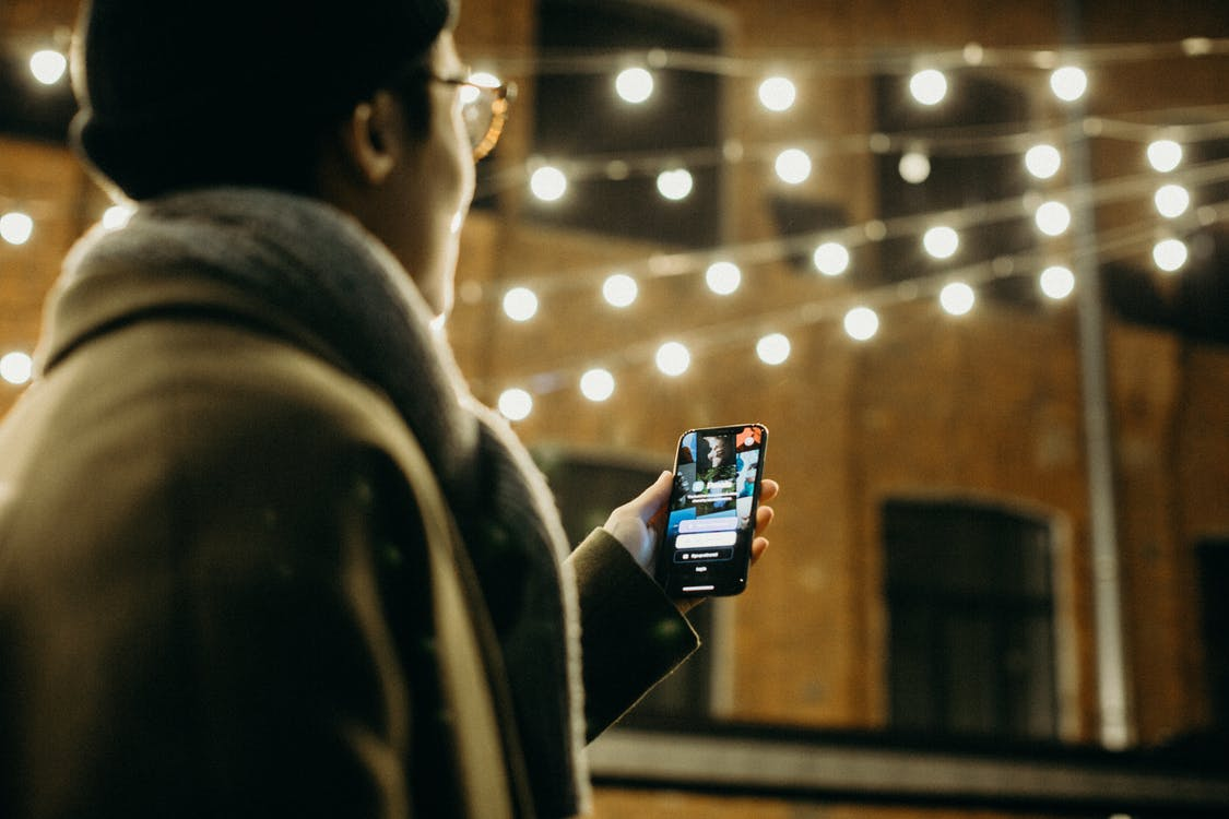 Selective Focus Photography of Man Using Smartphone Beside String Lights
