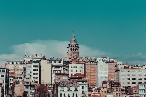 Old tower rising over modern buildings in city