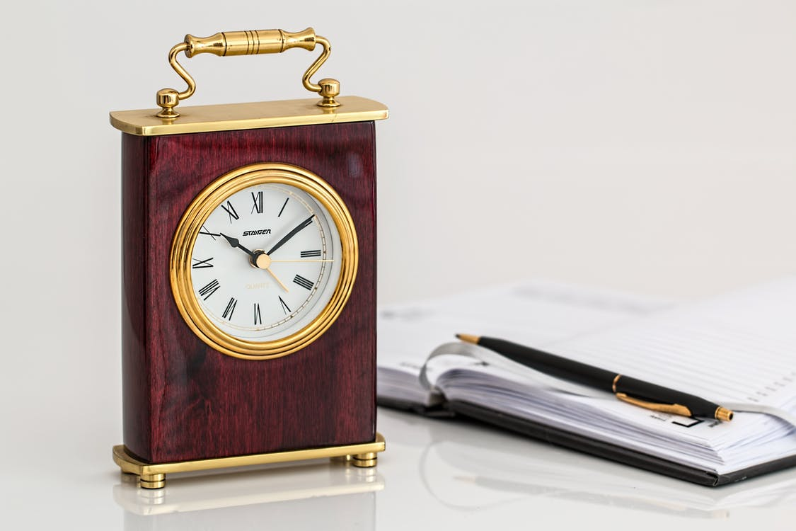 Brown and Brass-colored Desk Clock on White Surface Beside Black Click Pen on Opened Notebook