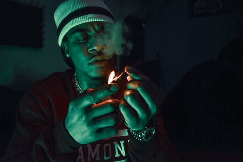 Crop frowning African American male in street style outfit  sitting in dark room and lighting cigarette