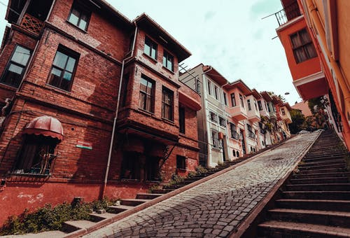 Street with residential buildings and cobblestone road on hill