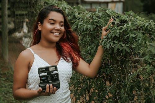 Photo of Woman Holding Polaroid Camera
