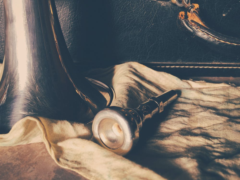 Silver Rod on Beige Cloth Beside Black Panel