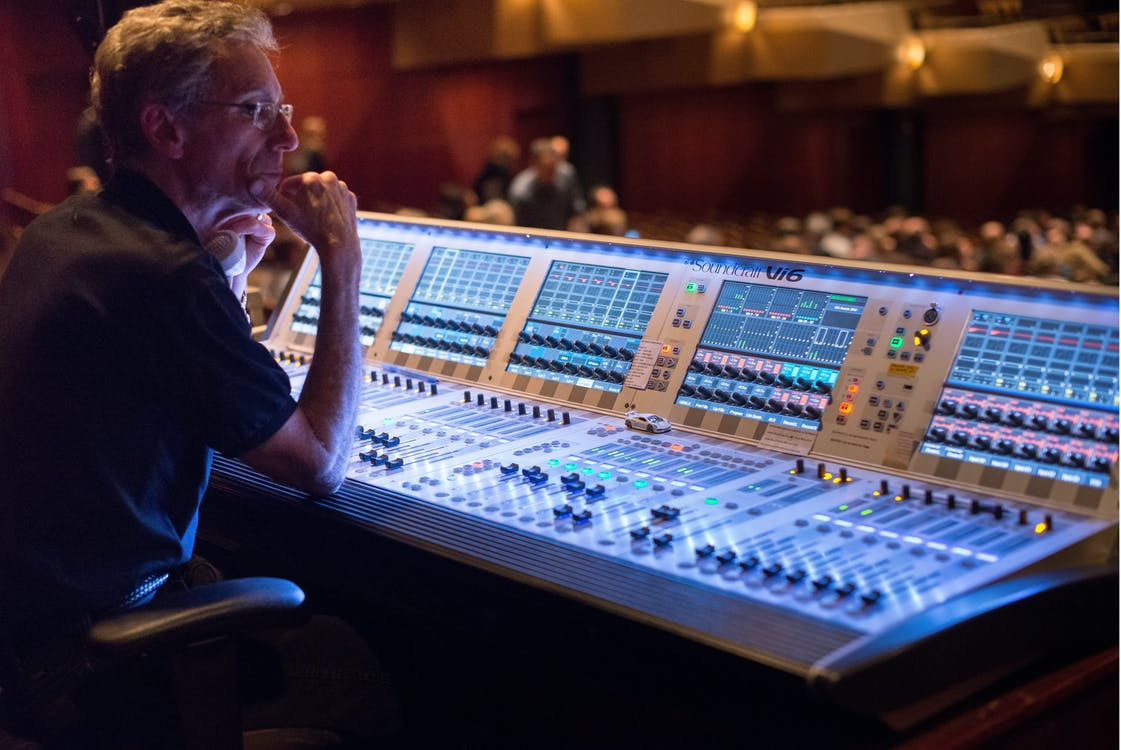 Man Sitting in Front of Audio Mixer