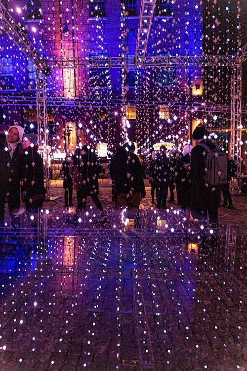 People Walking on Lighted Hallway