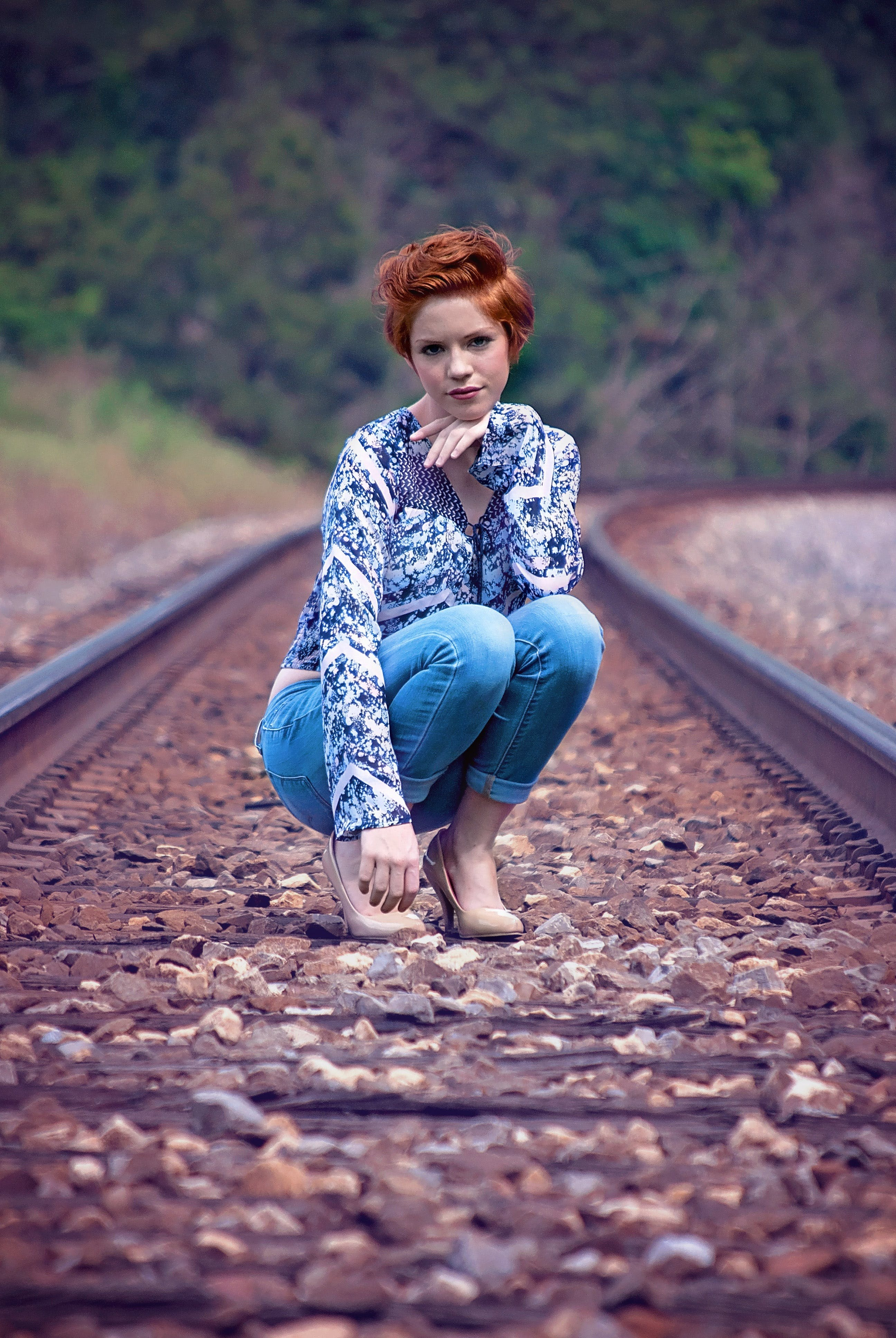 Woman Wearing Blue on Train Track during Daytime