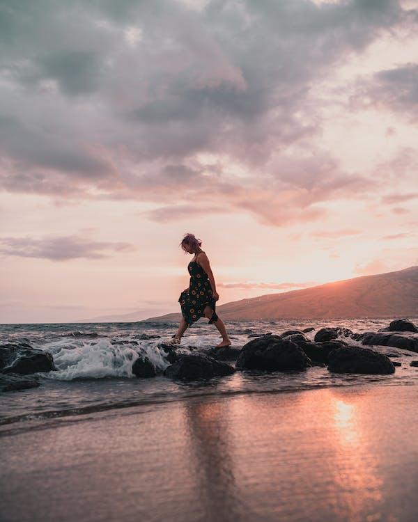 Woman Wearing Black Floral Dress Walking on Rocks Near Sea during Sunset