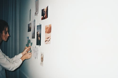Woman Putting Picture on White Wall