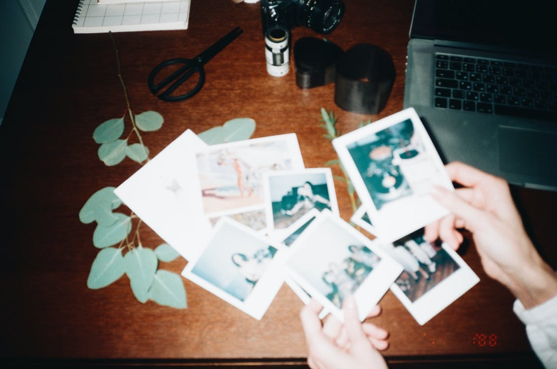 Person Holding Instant Photos