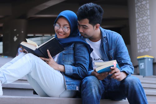 Man in Blue Denim Jacket Sitting Beside Woman in Blue Scarf Reading Book