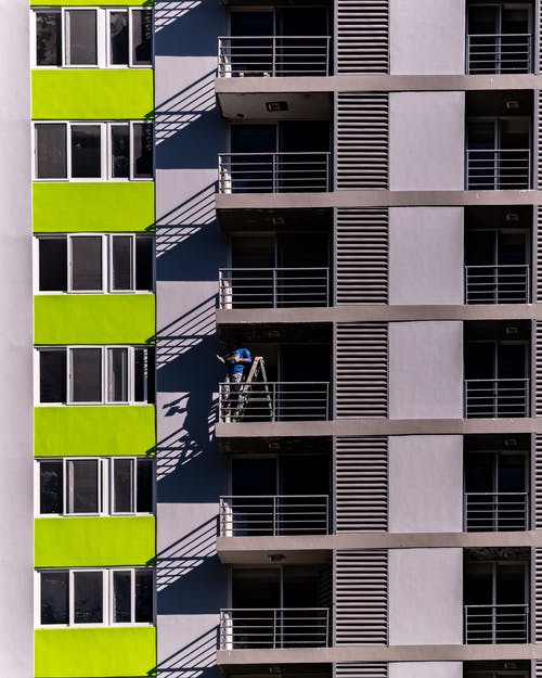 Man Standing On A Ladder On A Balcony Of A Building