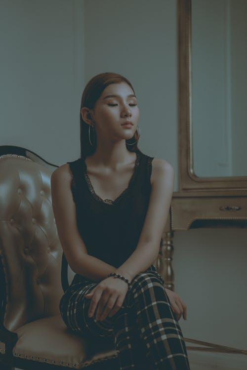 Woman in Black Top Sitting on Chair