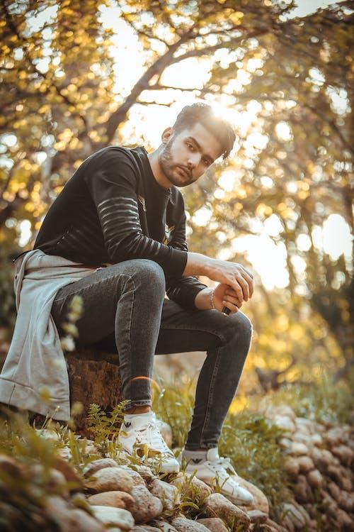Homem De Camisa Preta De Manga Comprida E Jeans Jeans Sentado No Tronco Da árvore