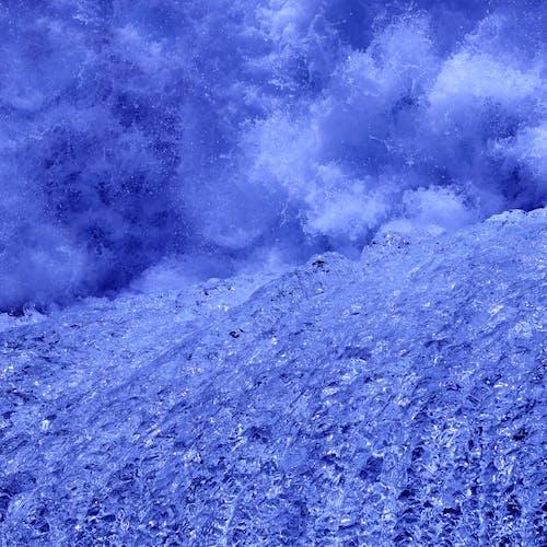 Shiny frozen violet mountain near splashing ocean in storm