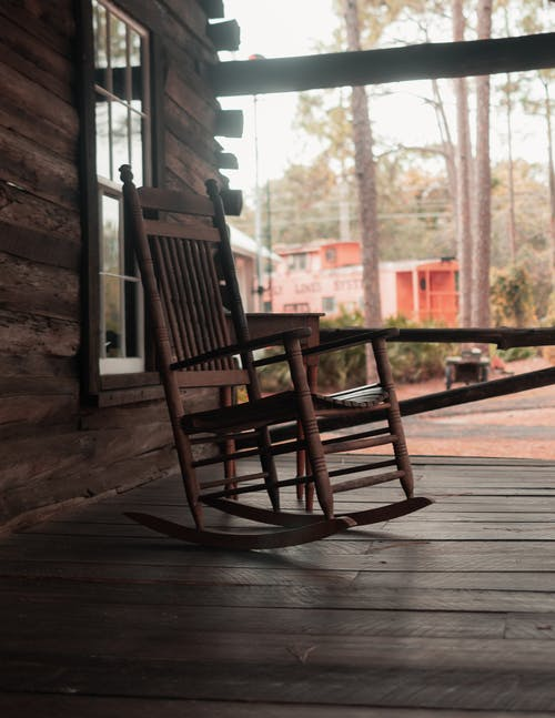 Wooden rocking chair located on terrace of wooden house with big window against wooden floor and trees and building in daytime