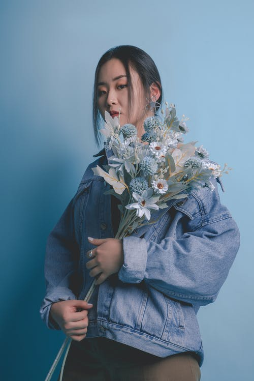 Woman in Blue Denim Jacket Holding White Flower Bouquet