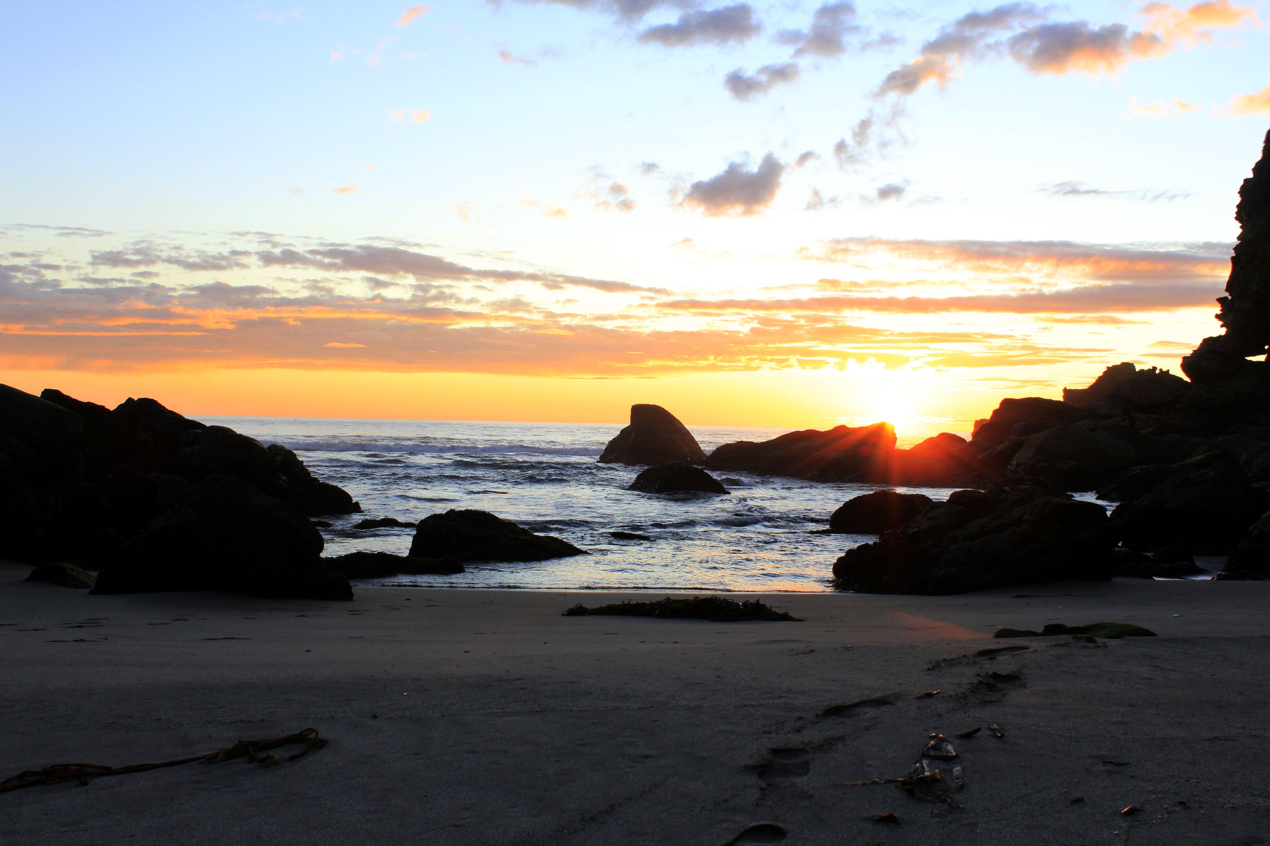 Beach and Rocks Under Orange Sunset