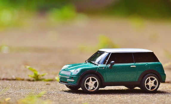 Green Scale Model Car on Brown Pavement