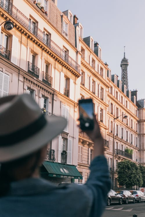 Man in Black Hat and Black Sunglasses Taking Photo of Building