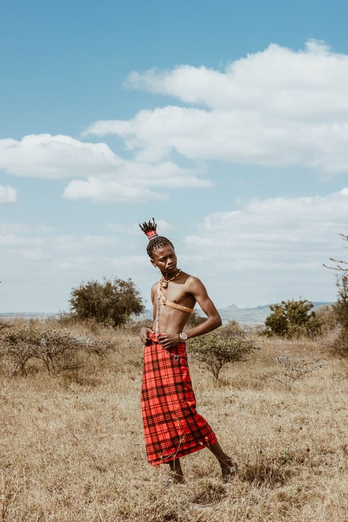 Man in Red and Black Checkered Skirt Standing on Dry Grass Field
