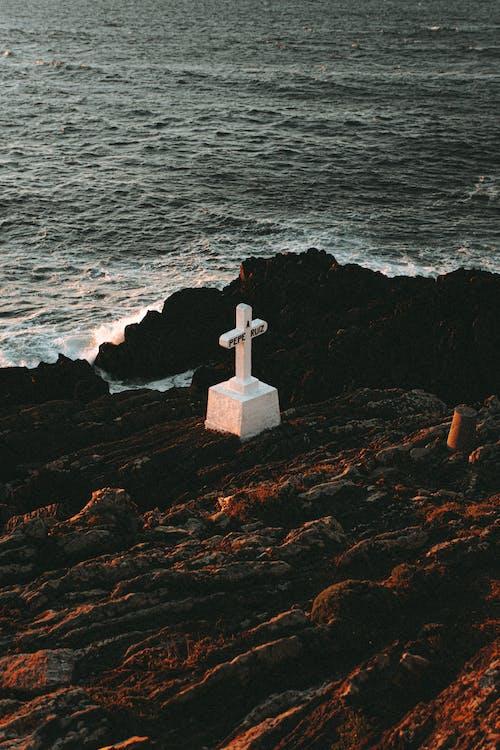 White Cross On Brown Rock Near Body Of Water