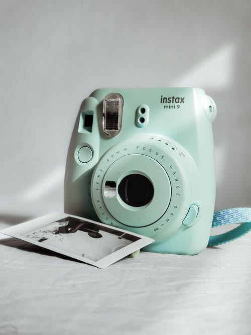 Teal and White Camera on White Table
