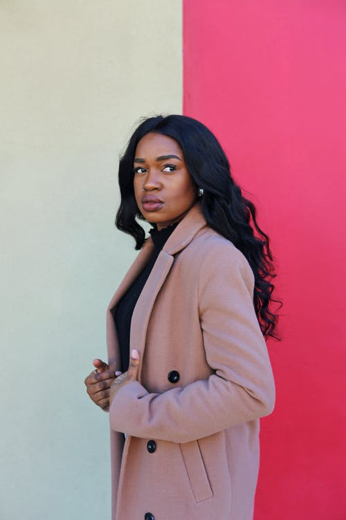 Woman in Brown Coat Standing Beside Red Wall