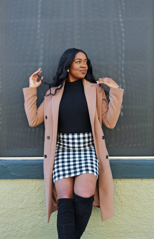 Woman in Black and White Checked Mini Skirt and Brown Coat