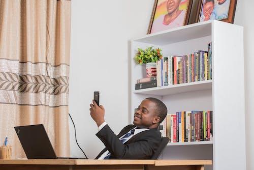 Gratis lagerfoto af afroamerikansk mand, bærbar computer, bøger, bogreoler