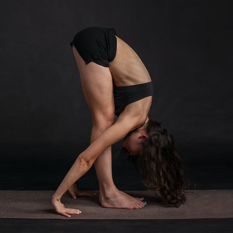 Woman Wearing Black Sports Bra Reaching Floor While Standing