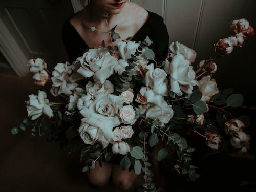 Woman in Black Dress Holding White Flower Bouquet