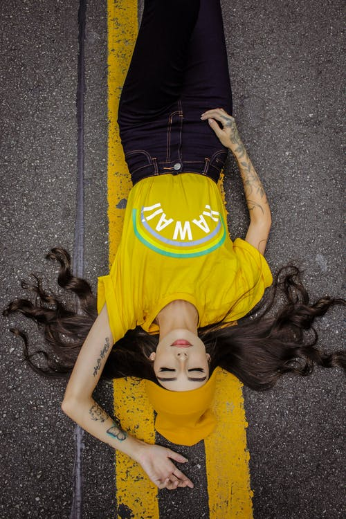 Woman in Yellow and Black T-shirt Lying on Grey Concrete Floor