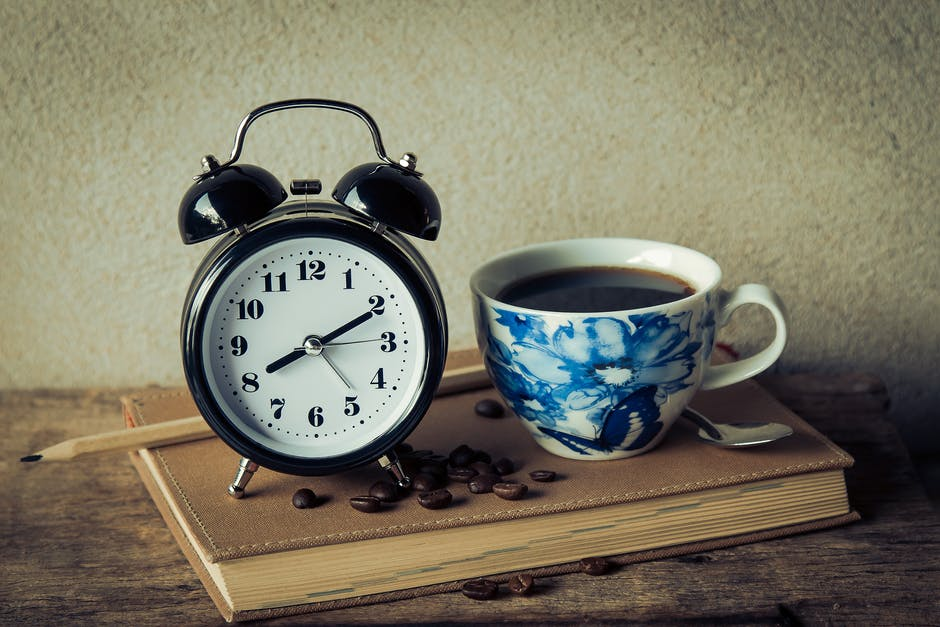 alarm clock, black coffee, book