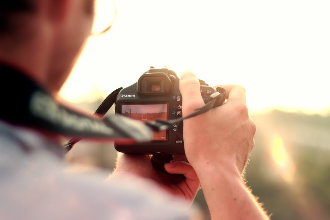 Man Holding Black Dslr Camera Standing in Front of the Sun