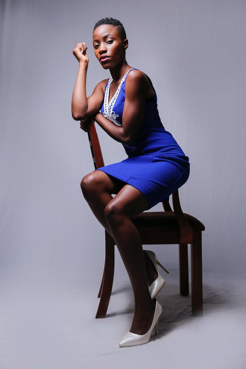 Woman in Blue Sleeveless Dress Sitting on Brown Wooden Chair