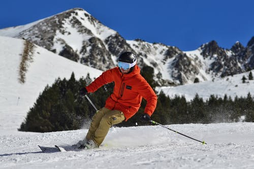 photo of a man in an orange jacket and beige trousers skiing