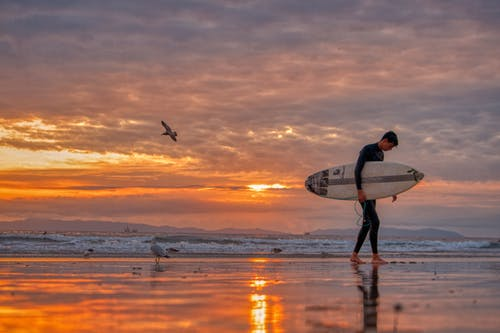 Man Walking on Beach Carrying White Surfboard during Sunset