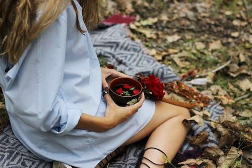 Gratis arkivbilde med blå skjorte, blomster, holde, kaffekopp