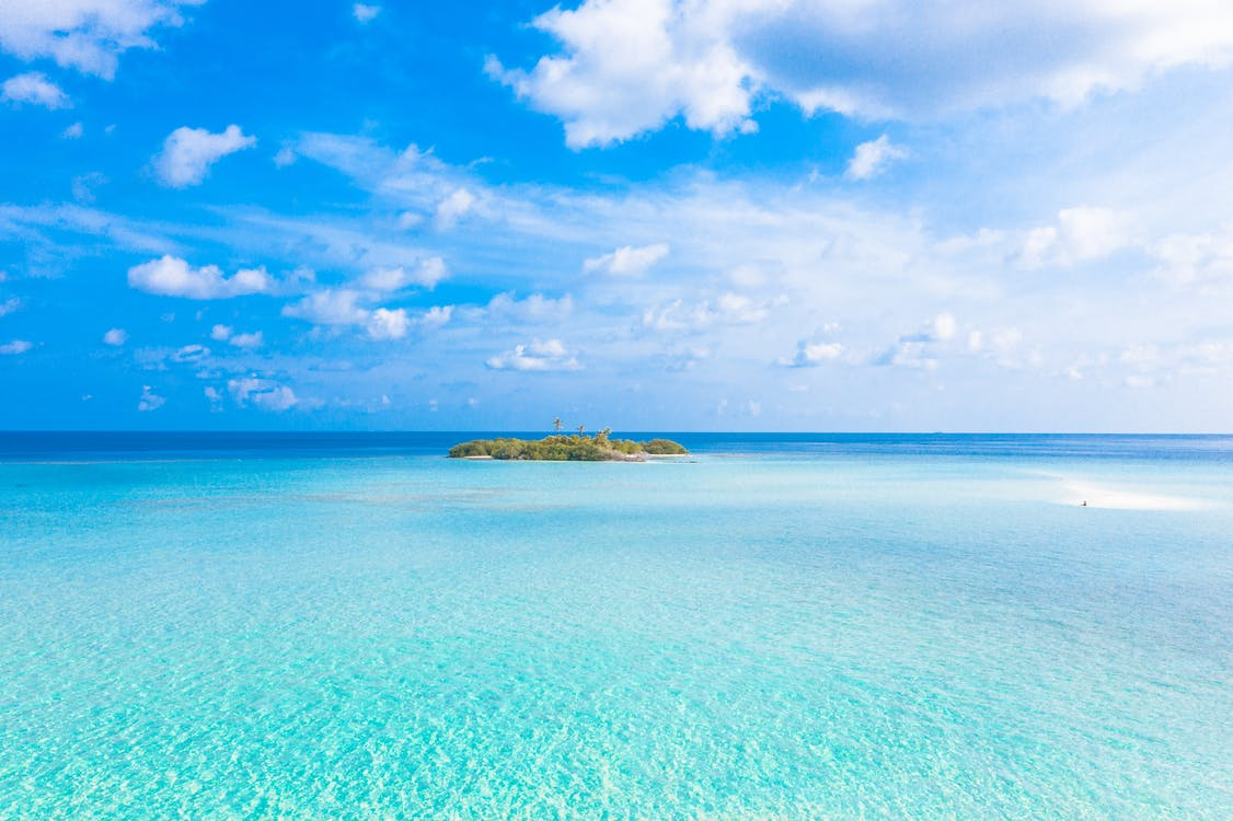 Island In The Middle Of The Sea Under Blue Sky And White Clouds