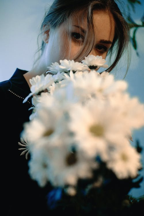 Woman in Black Shirt Holding White Flowers
