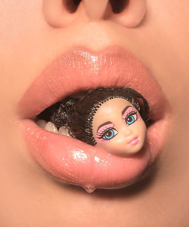 Close-up View Of A Person's Mouth With A Doll Head