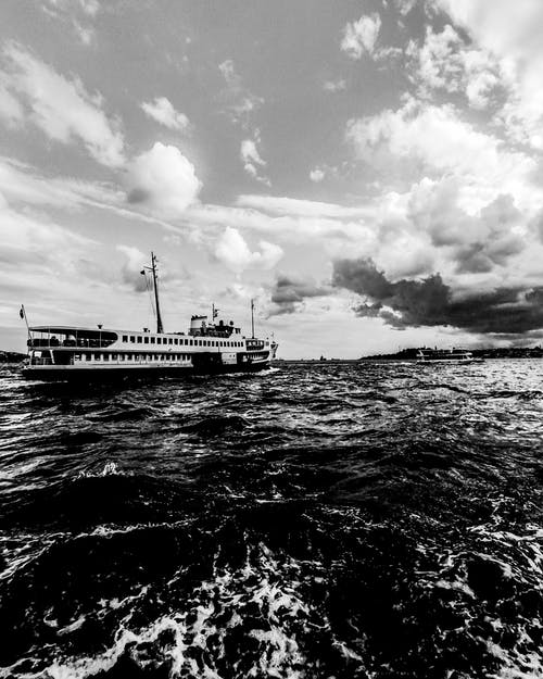 Grayscale Photo of Ship on Sea