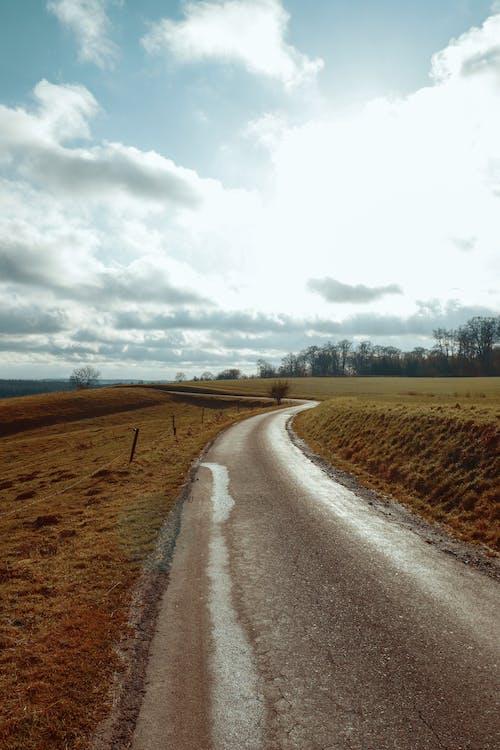 Jalan Aspal Kelabu Antara Lapangan Rumput Coklat Di Bawah Langit Berawan Putih
