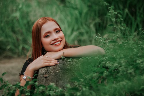 Photo of a red haired woman posing in green fields