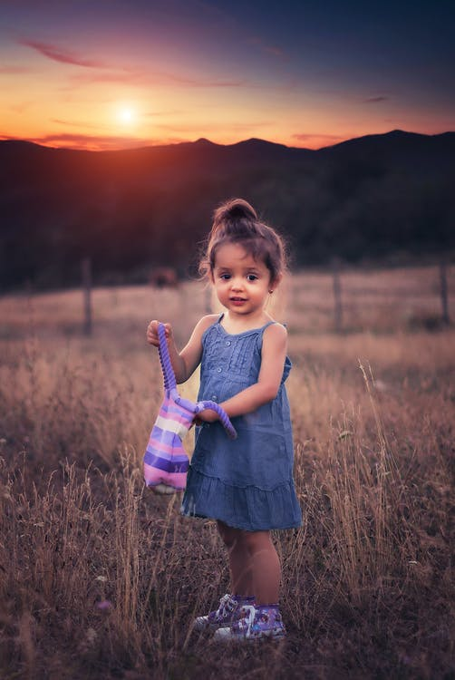 Girl in Blue Dress Standing on Grass Field during Sunset